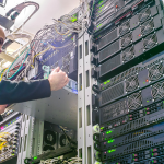 The engineer installs the new equipment in the server rack of the data center. The technical specialist works in the server room