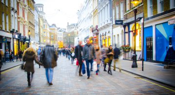 Shoppers walk down busy central London High Street