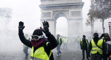 Riot Police uses a water canon and tear gas against demonstrators during a protest against the rising of the fuel and oil prices by people wearing yellow vests