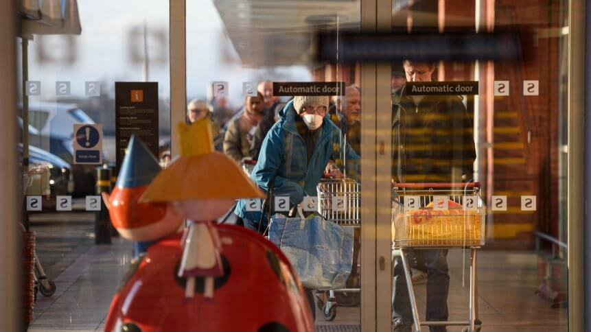 Shoppers queue before the 7am opening time to enter a Sainsbury's supermarket in Oldham, northern England, on March 20, 2020.