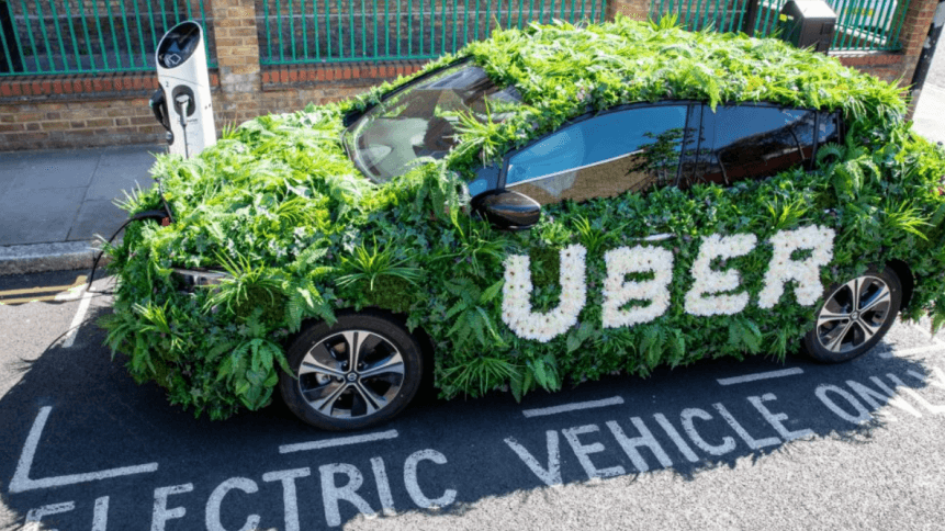 Uber electric taxi covered in green foliage